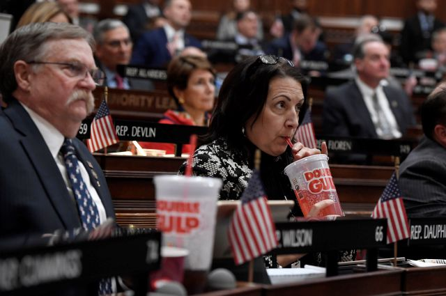 State Rep. Anne Dauphinais R-Killingly, takes a sip from a big gulp soda as Connecticut Gov. Ned Lamont delivers his budget address at the State Capitol in Hartford, Conn., Wednesday, Feb. 20, 2019. Lamont has proposed a tax on sugary drinks in his first budget. (AP Photo/Jessica Hill)
