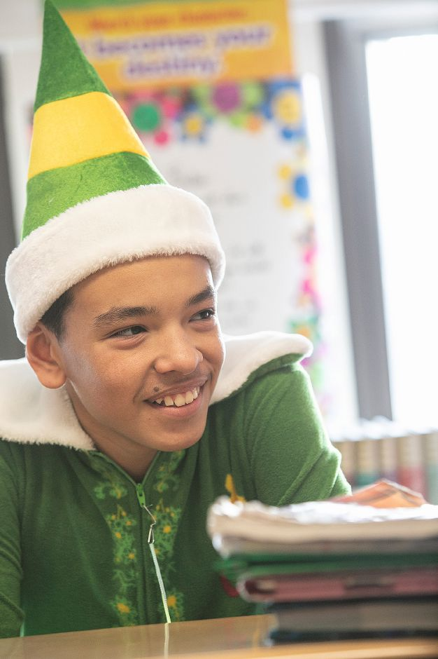 "Student Cristian Torres, 12, wears ""elf"" pajamas in his seventh-grade class during PJ Day for the Kids at Our Lady of Mount Carmel Elementary School in Meriden, Fri., Dec. 14, 2018. Students and staff participated in PJ Day for the Kids in support of patients at Connecticut Children's Medical Center. The one dollar donation per person is to honor children at the hospital who wear their PJs for days, weeks or longer while fighting cancer or other serious illnesses. Dave Zajac, Record-Journal"