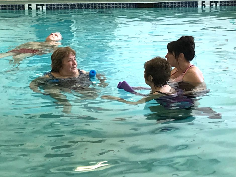 Instructor Phyllis Drescher talks with Jane Pinciaro and her helper Lauri Kapozzi while Howard Inglis floats in the background during a Parkinson's aquatic exercise class in the therapy pool at the Wallingford YMCA, 81 S. Elm St., Wallingford. |Ashley Kus, Record-Journal