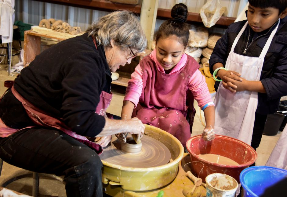 A Wesleyan pottery representative teaches pottery to Carmen Rogers, 8, of Meriden, at the Durham Fair on Friday, Sept. 28, 2018. | Bailey Wright, Record-Journal