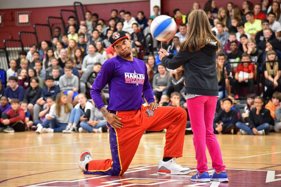 Harlem Wizards player Jordan Sutherland helps a student hold a spinning basketball during a preview assembly to their Oct. 6 show, while at North Haven Middle School on Tuesday, Sept. 25. | Bailey Wright, The Citizen