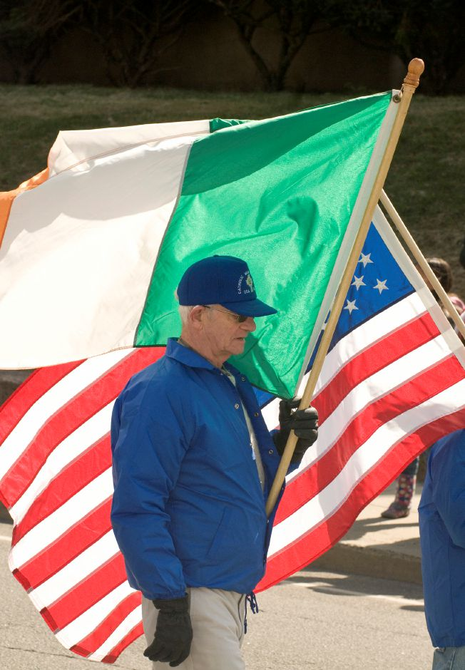 A member of the Catholic War Veterns Post 1116 holds an Irish flag during the St. Patrick