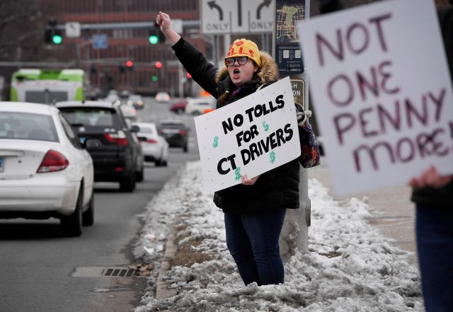 Hilary Gunn, of Greenwich, Conn., protests the idea of tolls on Connecticut roads outside the State Capitol after Connecticut Gov. Ned Lamont delivered his budget address in Hartford, Conn., Wednesday, Feb. 20, 2019. (AP Photo/Jessica Hill)