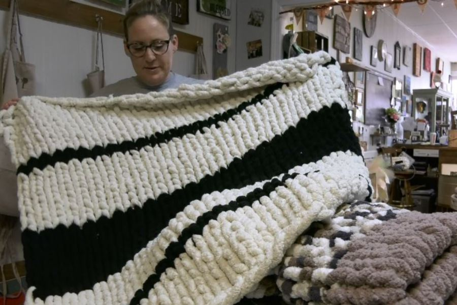 Stacey Tarasiewicz holds up a completed blanket. She will be hosting hand-knit blanket workshops this winter at her shop, Stacey T