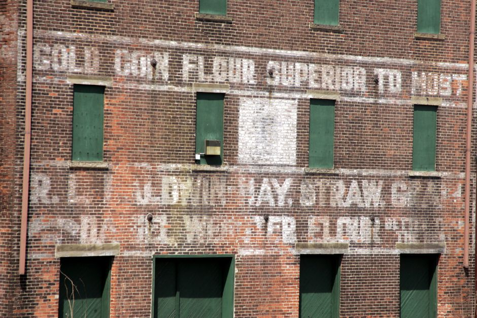 Rear of the Russell Hall Co. on North George St. in Meriden Fri., April 21 as seen from Center St. are these old ads for Gold Coin Flour and R.L.Baldwin-Hay, Straw, Grain, and for Daniel Webster Flour.