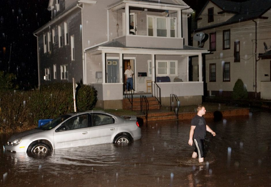 Anthony Bunnell of Meriden walks back across a flooded Summer Street after disengaging the emergency brake of his vehicle so it could be towed from about a foot of water Sunday evening December 12, 2010. Police closed the eastern section of the street using flares and cones. (Dave Zajac/Record-Journal)