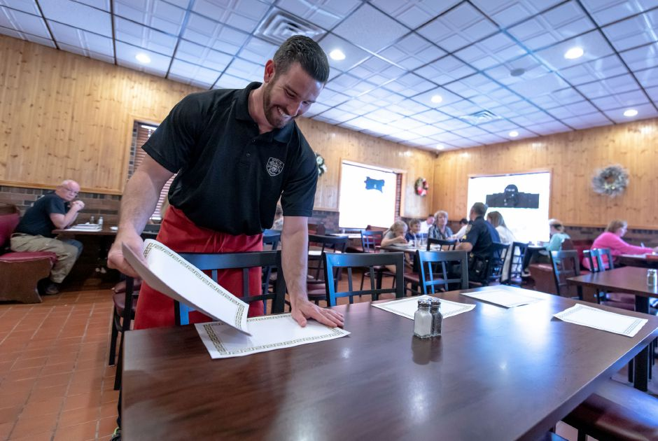 Berlin police Detective Ted Fuini sets tables during the department