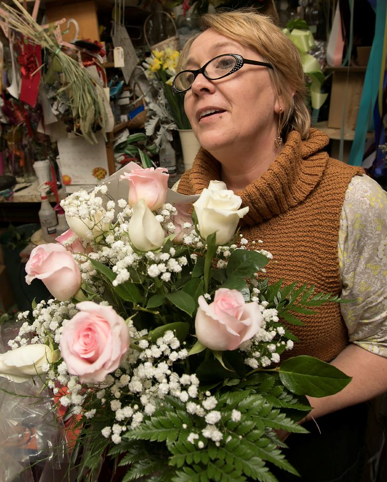 Nina Glinski, owner of Barnes House of Flowers, Inc. in Wallingford, carries a dozen pastel roses arrangement to the refrigerator for a Valentine