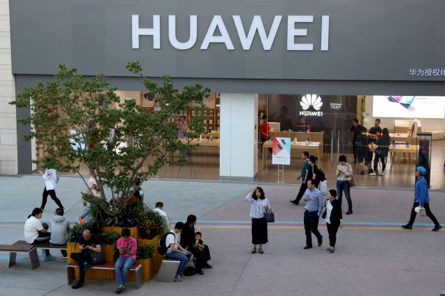 A woman gets her bearing outside a Huawei store in Beijing Monday, May 20, 2019. Google is assuring users of Huawei smartphones the American company