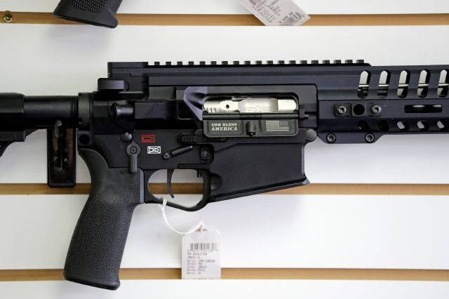 "FILE- In this Oct. 2, 2018, file photo, a semi-automatic rifle, with ""God Bless America"" imprinted on it, is displayed for sale on the wall of a gun shop in Lynnwood, Wash. Starting Tuesday, Jan. 1, 2019, no one under the age of 21 in Washington state will be allowed to purchase a ""semi-automatic assault rifle,"" under a voter-approved initiative that passed in November. (AP Photo/Elaine Thompson, File)"