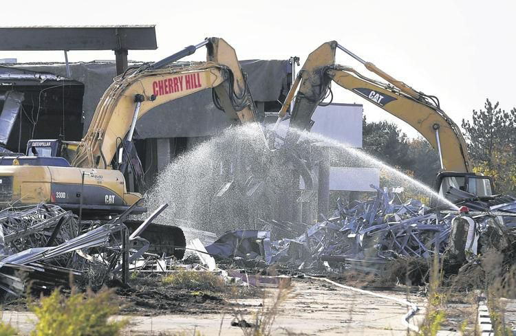 Two excavators grab at debris as a worker sprays water during the demolition of the former Showcase Cinemas in East Hartford on Monday afternoon. (Jessica Hill / Journal Inquirer)