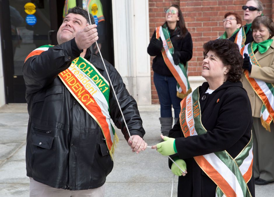 Brian Brennan, President of the AOH, left, and Doreen Roddy, President of the Ladies AOH, right, raise the Irish flag outside city hall in Meriden on St. Patrick