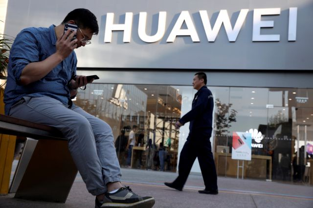 A man uses two smartphones at once outside a Huawei store in Beijing Monday, May 20, 2019. Google is assuring users of Huawei smartphones the American company