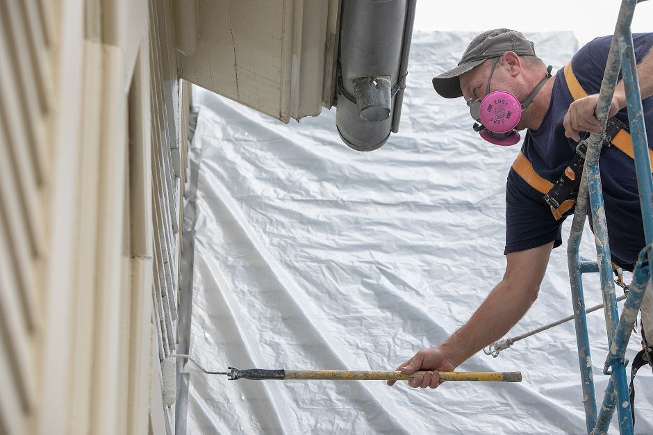 Dave Dixon, owner of Northeast Painting and Decorating rolls primer on the west side of Plantsville Congregational Church as renovations continue on the 1866 church, Tuesday, Oct. 9, 2018. Dave Zajac, Record-Journal