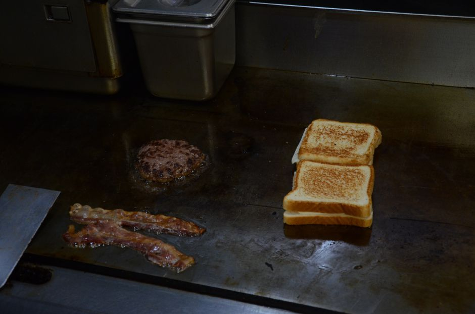 Preparing components for 2 Guys One Grill's signature CheeSin Squeezin Burger on April 9th, 2019. | Maxine Philavong, Special to the Record Journal.