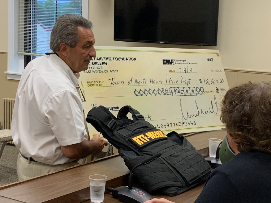 Fire commissioner Peter Criscuolo with a $12,500 check from Town Fair Tire and a ballistic vest.