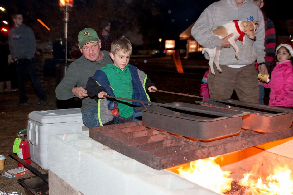 Ethan Gonzalez, 5, of Southington, roasts chestnuts with John Sommers, of Southington, at Plantsville