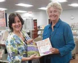 Pat LaTerza, Director of North Haven Memorial Library, receives donated books from Daytime Gardener, Jan Meinsen.