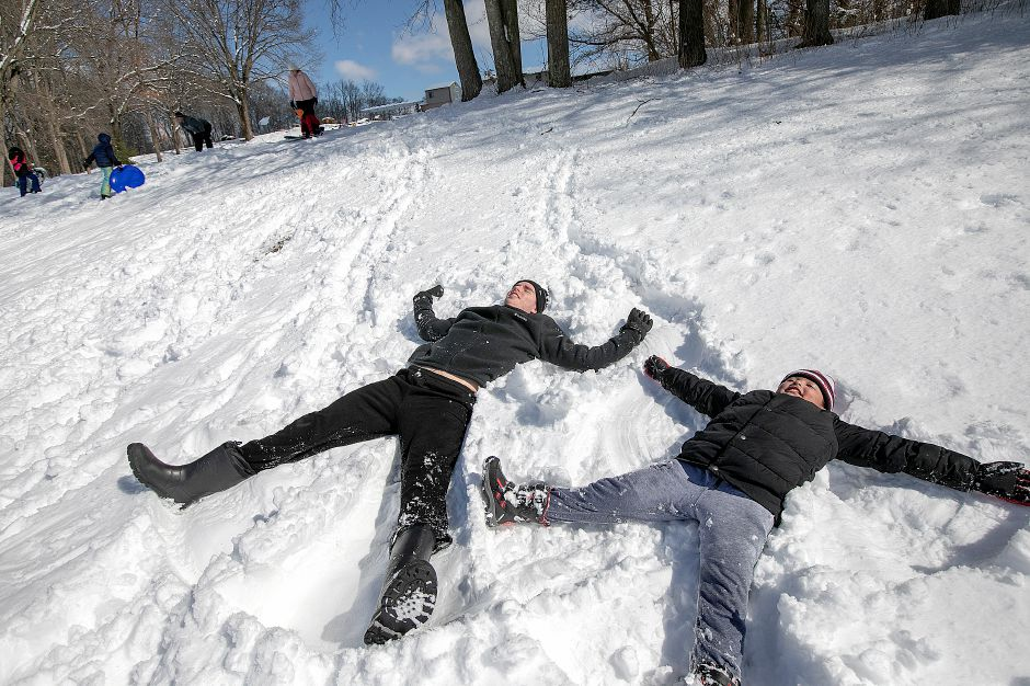 Jackson Thibeault, 16, and brother, Julian Thibeault-Bray, 8, of Southington, create snow angels at Panthorn Park in Southington on Monday.