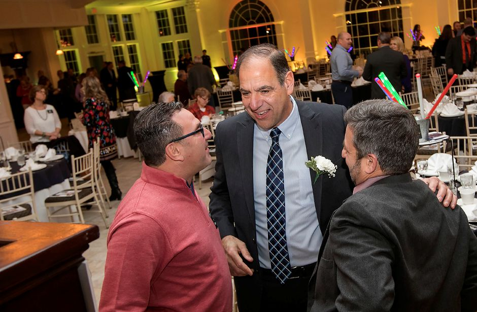 Mike DeFeo, center, greets friends, Ralph Campochiaro, left, and Mike Fasulo, both of Southington, during the Southington-Cheshire Community YMCA's 89th annual Celebration and Recognition event at the Aqua Turf Club in Southington, Tuesday, Feb. 6, 2018. DeFeo, Parks and Recreation board vice chairman, received the YMCA