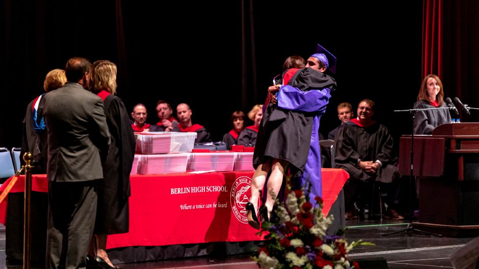 A student gives a staff member a hug during the Berlin High School graduation cermony, held at Central Connecticut State University on June 16, 2019. | Devin Leith-Yessian/Record-Journal