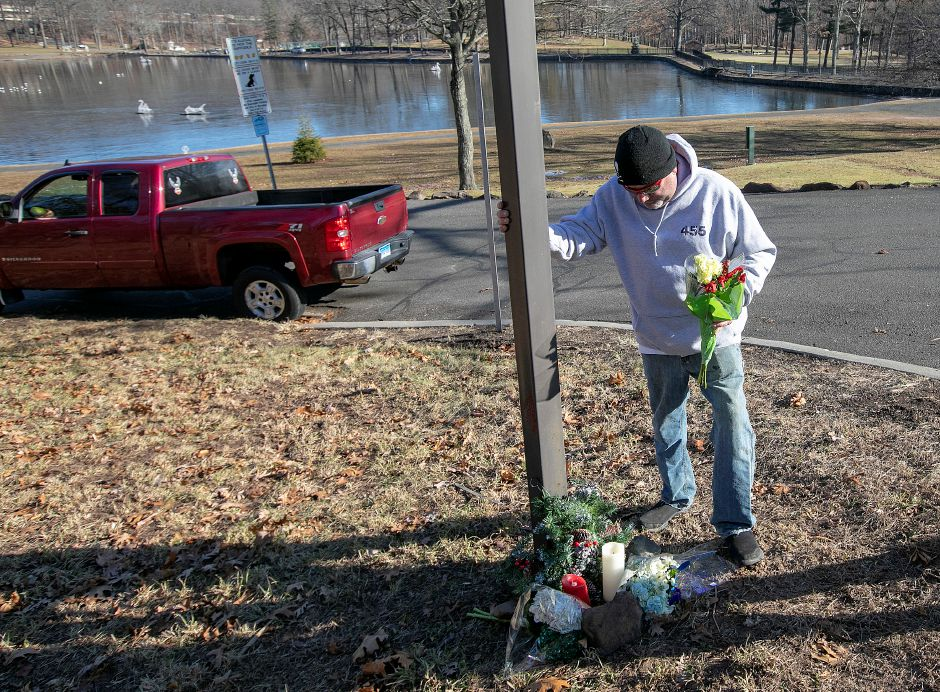 John Muli, of Meriden, places flowers at a roadside memorial for long-time friend, Leopold Dishereits, 53, at the entrance to Hubbard Park in Meriden, Mon., Dec. 10, 2018. Dishereits died after his motorcycle collided with an SUV at the entrance to Hubbard Park Sunday night. Dave Zajac, Record-Journal