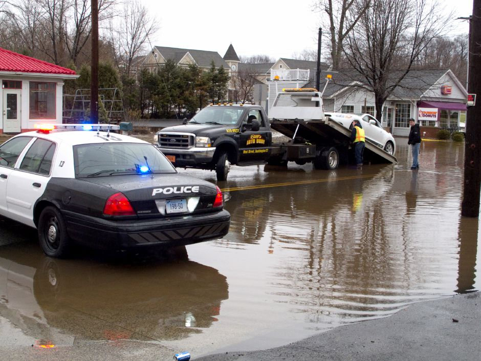 A towing crew pulls a car that stalled out of the water on Main Street (Rt. 10) in Planstville Monday morning, March 7, 2011. Heavy rains lead to flooding and closure of several roads in Southington. (Christopher Zajac/Record-Journal)