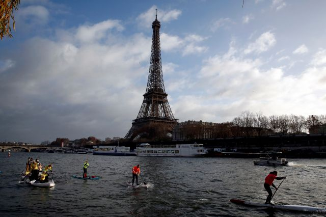 FILE - In this Dec.9, 2018 file photo, competitors paddle on the Seine river in front of the Eiffel Tower in Paris. The Eiffel Tower press office said Monday May 20, 2019 an unidentified individual tried to scale the near-300 meter (near-328 yard) monument on Monday afternoon but it wasn