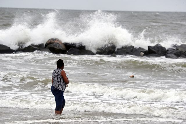 Gwen Patterson watches as waves crash ashore at Buckroe Beach in Hampton, Va., Thursday, Sept. 13, 2018 as Hurricane Florence approaches the coast. (Jonathon Gruenke/The Daily Press via AP)