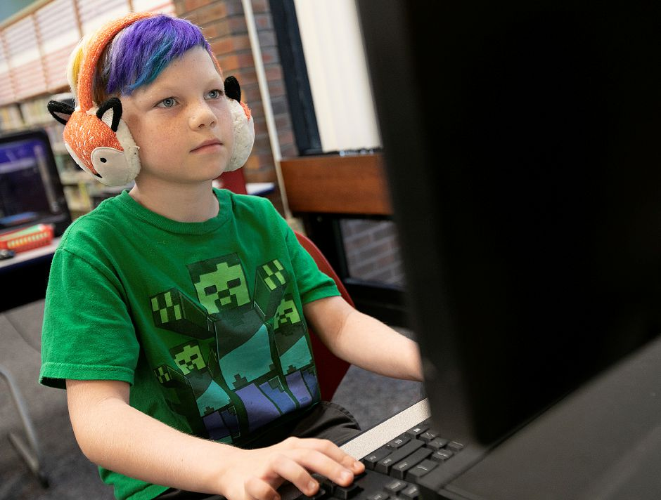 Devon Yineman, 7, of Meriden, dons a set of fox head muffs while playing a video game in the Children