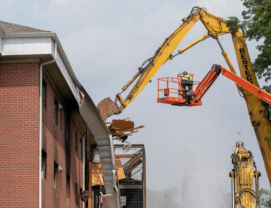 A worker on a lift helps guide a demolition excavator that claws at the roof of a building in the former Mills Memorial Apartments complex in downtown Meriden, Friday, August 17, 2018. Dave Zajac, Record-Journal