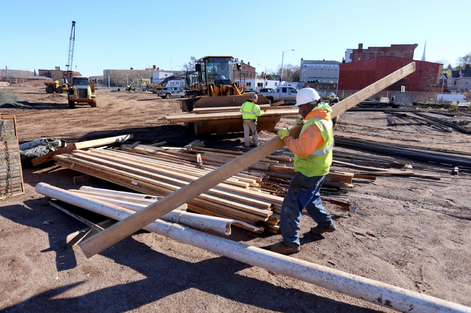James Yearby, foreground, Marco Ovalle, rear left, and Tyler White, rear right, of LaRosa Construction move lumber at the Meriden Hub site Wednesday Nov. 19, 2014. | Richie Rathsack/Record-Journal