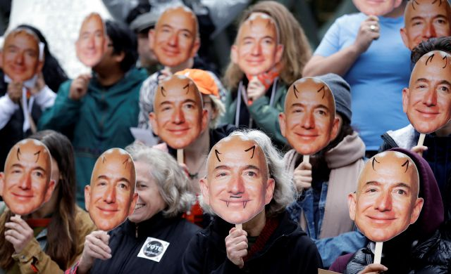 FILE - In this Oct. 31, 2018, file photo, demonstrators hold images of Amazon CEO Jeff Bezos near their faces during a Halloween-themed protest at Amazon headquarters over the company