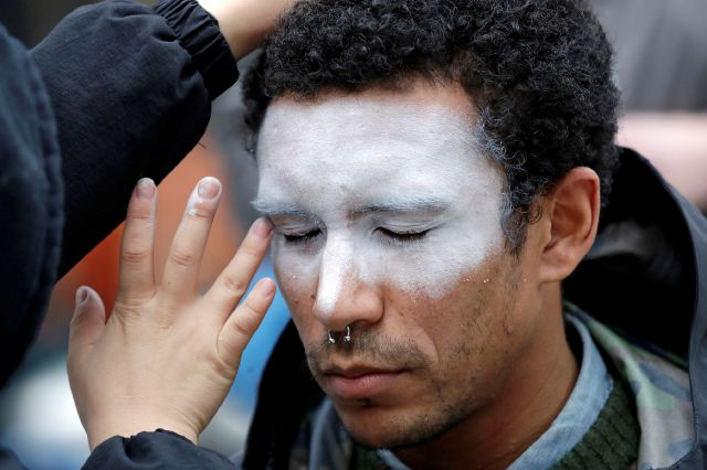 FILE - In this Oct. 31, 2018, file photo, a man, who declined to be identified, has his face painted to represent efforts to defeat facial recognition during a protest at Amazon headquarters over the company