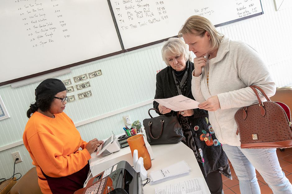 Coleen Murphy, of Meriden, right, and mother, Donna Casserino, of Westbrook, center, look over a menu as  owner Duangjai Shuster takes their order.