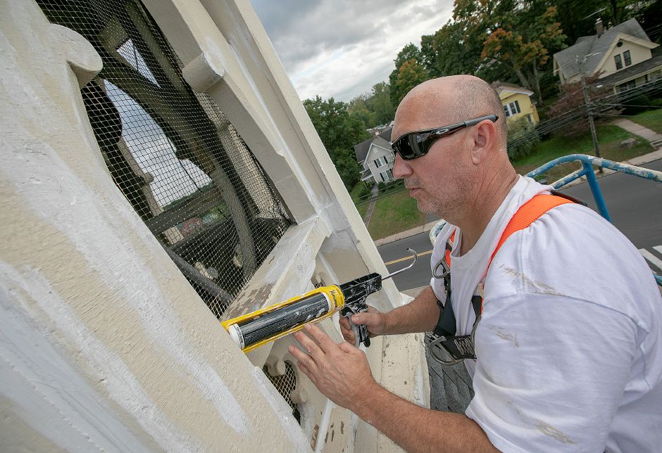 Painter Ronald Hepp, owner of Ronald J. Hepp Restoration, caulks the steeple of Plantsville Congregational Church as renovations continue on the 1866 church on Tuesday. Dave Zajac, Record-Journal