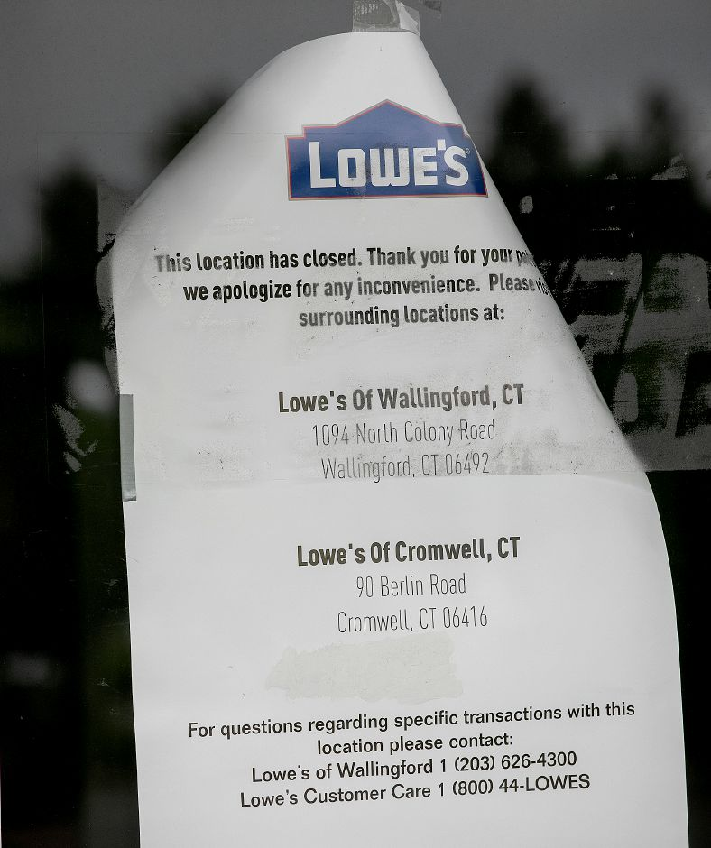 A closure notice remains on the window of the former Lowe