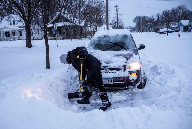 Adam Fischer shovels out his vehicle to go to work Monday, Jan. 28, 2019, in Rochester, Minn. Heavy snow and gusting winds created blizzard-like conditions Monday across parts of the Midwest, prompting officials to close hundreds of schools, courthouses and businesses, and ground air travel. (Joe Ahlquist/The Rochester Post-Bulletin via AP)