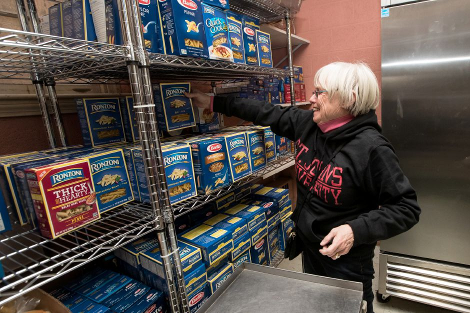 Mary Lyons stacks the pantry shelves with pasta Saturday during the Kiwanis Club