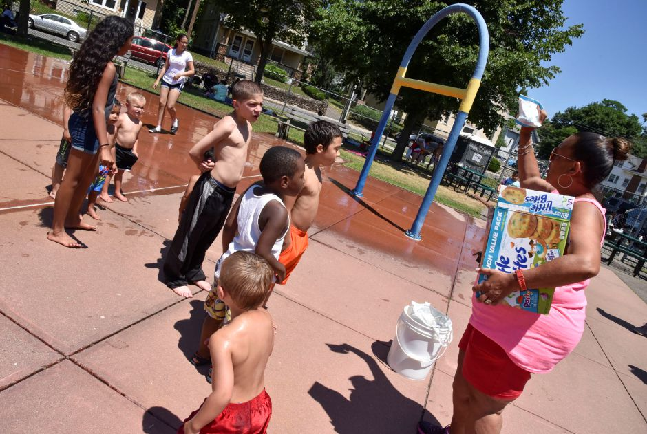Meriden Splash Pad Supervisor Eva Kim Marquez hands out snacks to the kids gathered at City Park on Tuesday, July 9, 2019. | Bailey Wright, Record-Journal