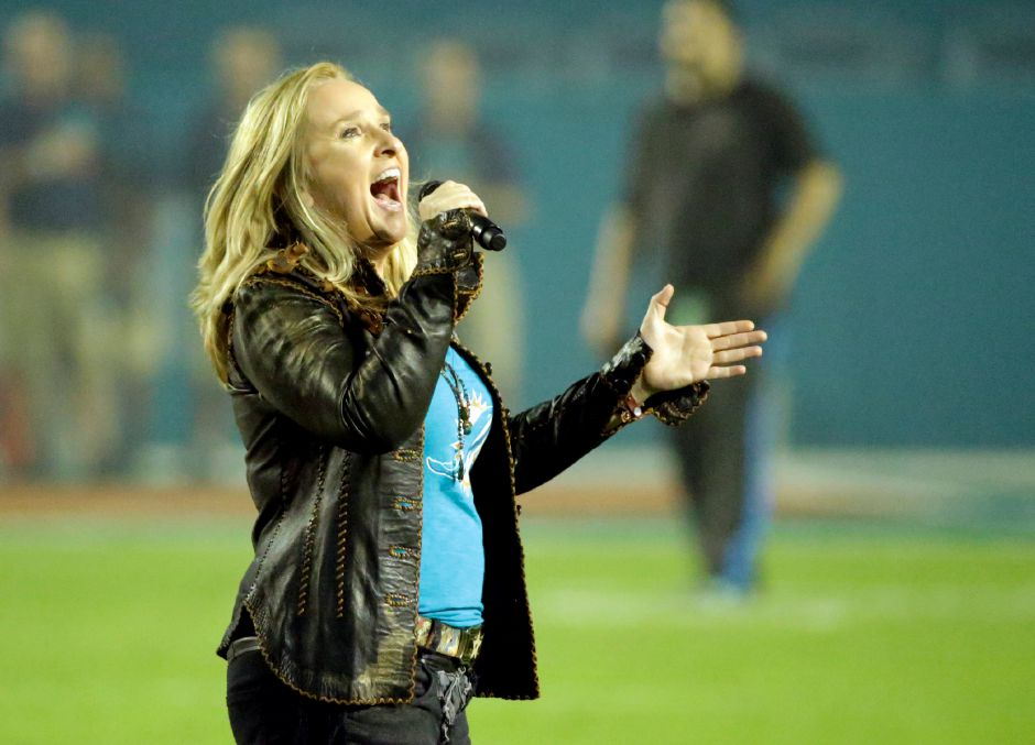 Singer Melissa Etheridge sings the National Anthem before an NFL football game between the Miami Dolphins and the New York Giants, Monday, Dec. 14, 2015, in Miami Gardens, Fla. (AP Photo/Wilfredo Lee)