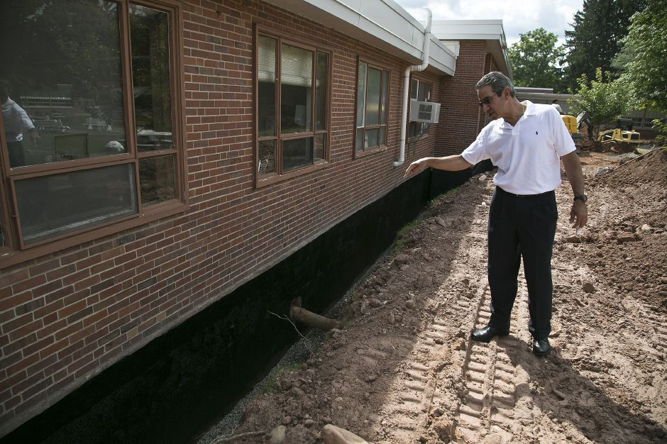FILE PHOTO: Vincent J. Masciana, Director of Management Services, explains the work to install better drainage around the perimeter of the courtyard in Cheshire High School, July 31, 2013. | (Christopher Zajac / Record-Journal)