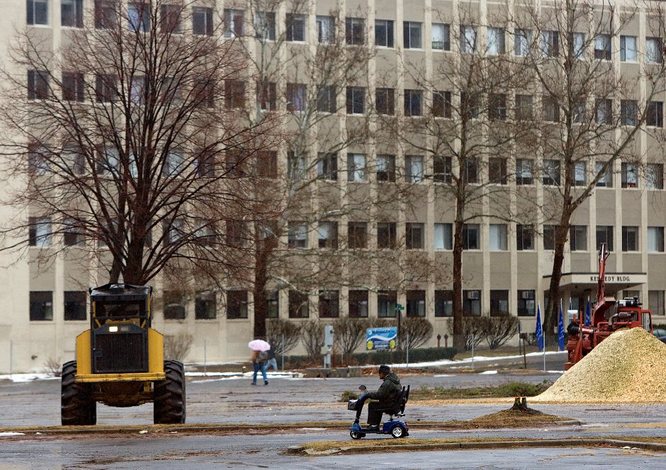 A man on a mobility scooter rides through the HUB as construction crews continue removal of several trees on the site, Monday, January 6, 2014. | Dave Zajac / Record-Journal