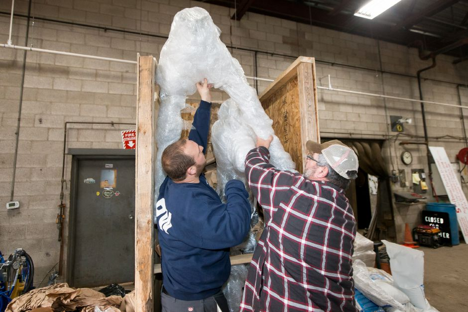Erik Santarsiere left and Gabe Calandra unpack a lighted horse and deer to add to the town
