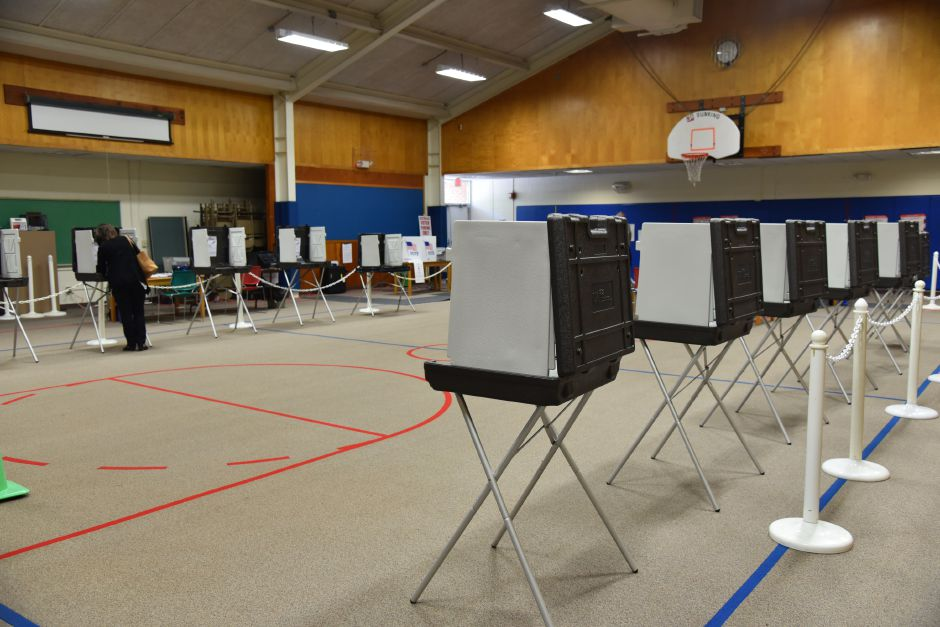 FILE PHOTO – Volunteers man near-empty stalls at the former Korn School building, where voting on Regional School District 13