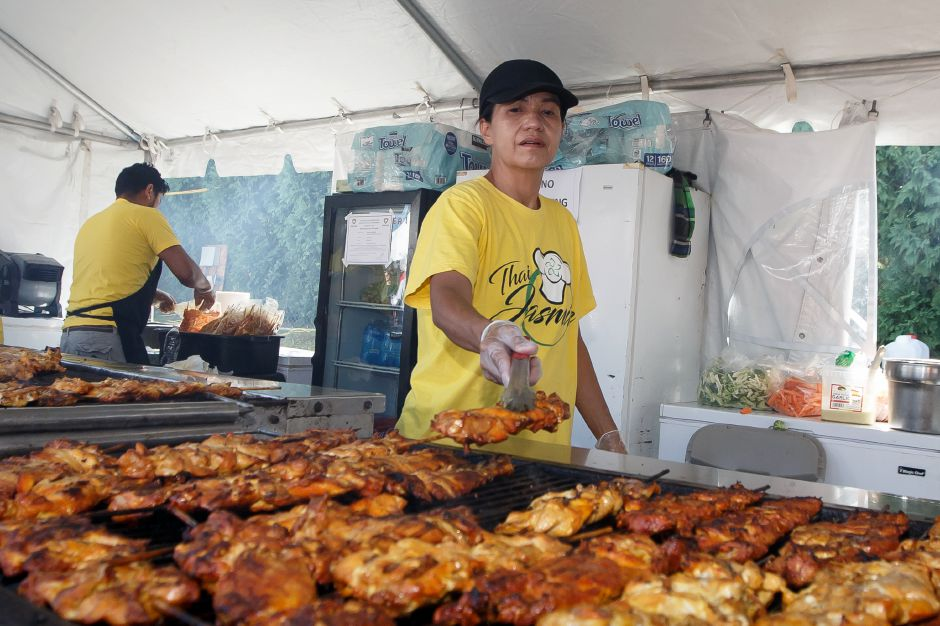 Napa Wongchai of Thai Jasmine turns some chicken on the grill Saturday during the Southington Apple Harvest Festival in Southington September 29, 2018 | Justin Weekes / Special to the Record-Journal