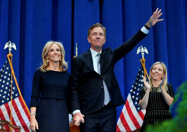 Connecticut Gov. Ned Lamont waves as he stands with wife Annie after taking the oath of office, Wednesday, Jan. 9, 2019, inside the William A. O