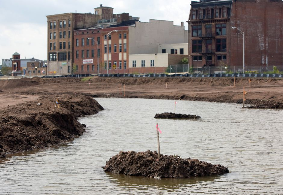 Surface water runoff fills a retention area running through the Hub site in Meriden, Tuesday, September, 2, 2014. The small staked islands in the channel show the center of the future brook. | Dave Zajac / Record-Journal