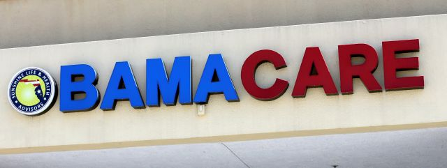 "File- This May 11, 2017, file photo shows an Obamacare sign being displayed on the storefront of an insurance agency in Hialeah, Fla. A conservative federal judge in Texas on Friday, Dec. 14, 2018, ruled the Affordable Care Act ""invalid"" on the eve of the sign-up deadline for next year. But with appeals certain, even the Trump White House said the law will remain in place for now. In a 55-page opinion, U.S. District Judge Reed O'Connor ruled Friday that last year's tax cut bill knocked the constitutional foundation from under ""Obamacare"" by eliminating a penalty for not having coverage. The rest of the law cannot be separated from that provision and is therefore invalid, he wrote. (AP Photo/Alan Diaz, File)"