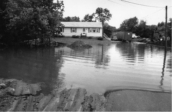 File photo - A house on West Johnson Avenue in Cheshire had a flooded lawn and driveway June 6, 1992.